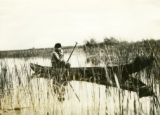 Poland, fisherman in canoe