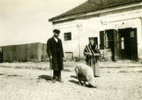 Poland, peasants on sidewalk with white hog