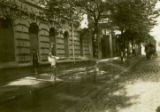 Lithuania, man watering the street with hose