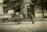 Lithuania, man pushing cart down street