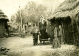 Belarus, mother and child standing next to thatched building