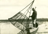 Belarus, man fishing in canoe with large conical fishing net