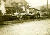 Poland, farmer transporting milk containers by wagon