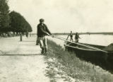 Belarus, men poling boat along bank