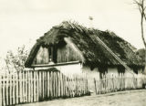 Poland, wooden house along the road with thatched roof