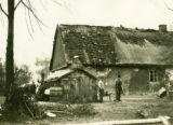 Poland, two men standing in front of barn