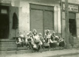 Ukraine, women sitting on store steps