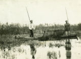 Poland, two men fishing in canoe