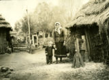 Belarus, mother and child standing next to granary