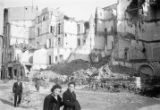 Italy, people walking past bomb damaged buildings in Livorno