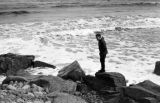 Canada, John Forman [Foreman] standing on rocky shore in Nova Scotia