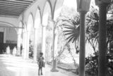 Mexico, girl standing in portico at Turner Hodge School in Mérida