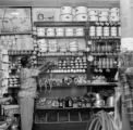 Puerto Rico, man stocking shelves at general store in Utuado