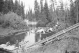 Canada, conveyor and pulp wood floating in river in Ontario Province