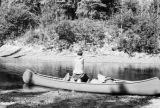 Ontario, Gil scratching his back in canoe at camp below upper Floodwood River