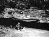 Preston County (West Virginia), man sitting under Greenbrier Limestone outcrop along Cheat River