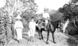 El Salvador, two boys standing next to a boy on a horse in La Unión