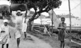 Martinique, children and porters near hanging fishing nets in La Trinité