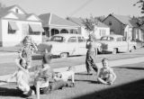 Canada, children playing on front lawn in Winnipeg