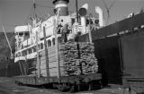 Canada, workers unloading lumber from ship on Vancouver Island
