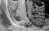 Canada, woman repairing nets at Vancouver harbor