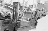 Canada, men unloading cargo at dock in Lunenburg
