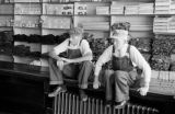 Canada, two elderly men sitting on counter of shop in Lunenburg