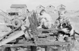 Canada, two boys with dog on farm equipment in Assiniboia