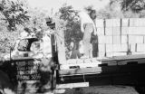 Canada, men unloading crates from truck in Vancouver