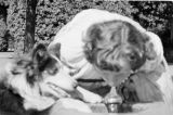 Canada, woman and dog drinking from water fountain in Vancouver