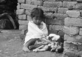 Mexico, girl sitting against building with puppy