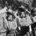 Guatemala, three girls carrying jugs in village
