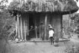 Haiti, children in front of thatched roof house on farm in Ouest department