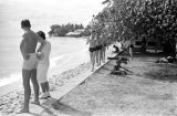 Guam, men walking along beach