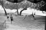 Guam, children walking past tent in park