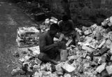 Chongqing (China), laborers chipping off mortar from bricks of bombed buildings
