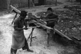 Chongqing (China), laborers splitting a wood board with a saw