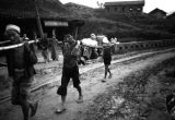 Chongqing (China), laborers carrying a man in a sedan chair