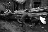 Chongqing (China), laborers hauling supply of bamboo on cart