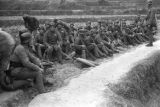 China, soldiers sitting beside path, possibly Japanese prisoners of war