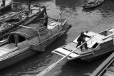 Shanghai (China), men steering sampans near dock on river