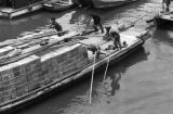 Shanghai (China), men steering fully loaded sampan on river