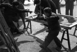 Shanghai (China), children helping man drill hole into wooden frame