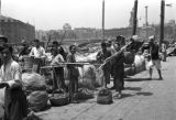 Shanghai (China), people at riverfront with baskets and bundles of goods