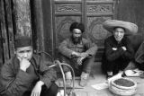 China, men sitting in front of building