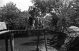 China, people standing on pedestrian bridge over canal
