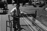 China, boy using rack to wind thread