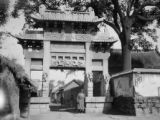 China, woman standing under ornate gate