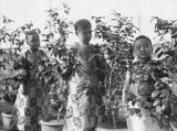 China, two dancing girls with younger sibling stand next to potted plants