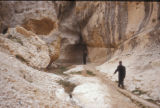 Malula (Syria), man standing at the mouth of a cave